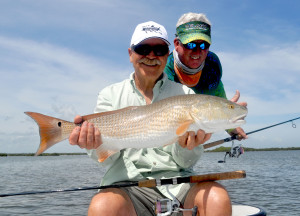 Long time fishing buddies celebrate a nice Redfish from Mosquito Lagoon.